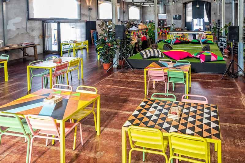 Café Naves en el que se ven muchas mechas coloridas y co elementos geométricos, plantas y espacios verdes.