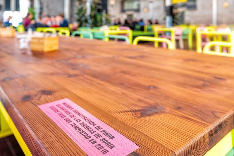 Mesa de madera con una placa que indica que se uso madera de árboles caídos de la sierra de Soria.