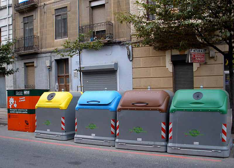 Cuatro contenedores de reciclaje, uno amarillo, otro azul, otro marrón y otro verde.