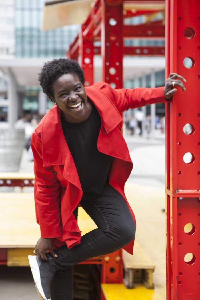 Mujer afroamericana con una chaqueta roja riéndose.