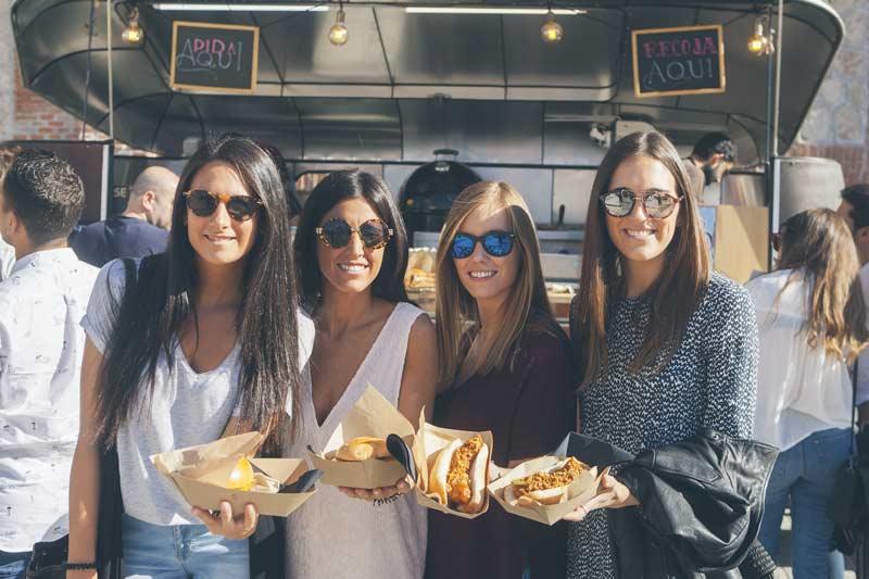 Cuatro mujeres con comida en la mano de los food trucks de Femme Creators.