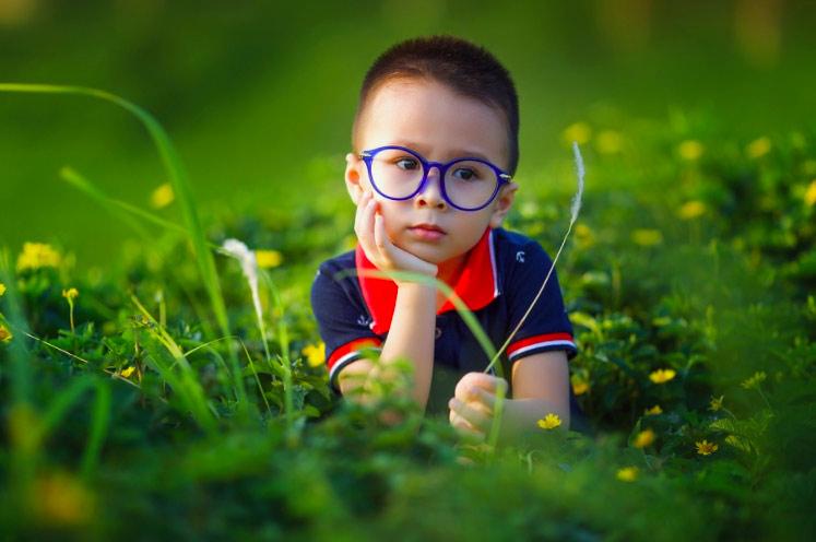 niño con gafas azules en jardín