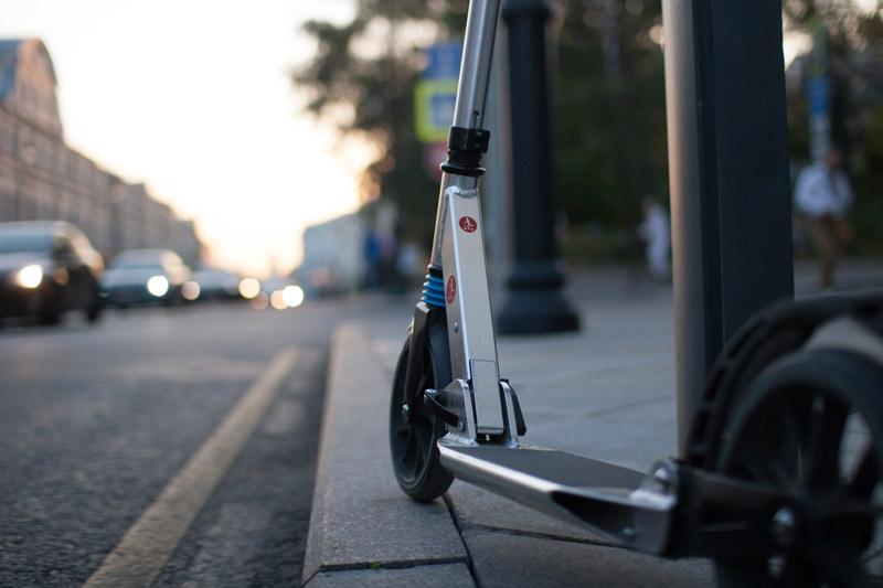 Patinete gris aparcado en la acerca al lado de una farola