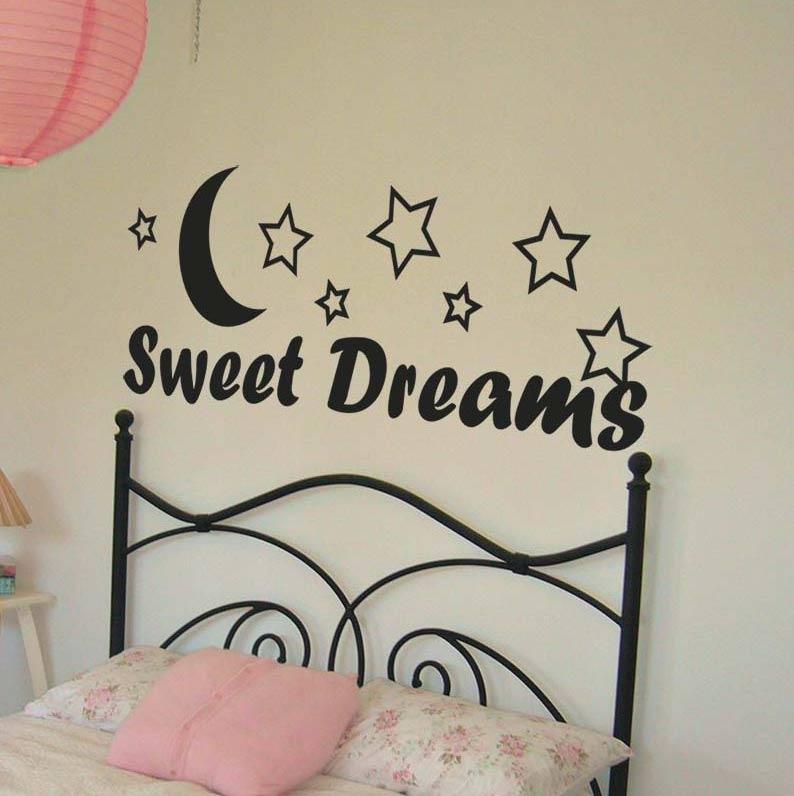 Vinilo negro Sweet Dreams en pared de habitación infantil sobre cabecero de forja negro y pared blanca